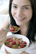 Woman eating healthy cereal Stock Photos