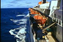 QE2 side shot from bridge wings, sea wash, tilt up, lifeboats & stack, medium Stock Footage
