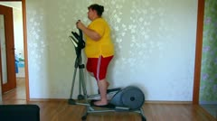 Overweight woman exercising on trainer ellipsoid Stock Footage