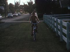 Boy biking across a lawn - Vintage 16mm - stock footage
