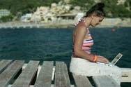 Happy female friends sitting on pier with laptop computer, dolly shot Stock Footage