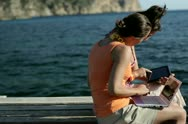 Happy female friends sitting on pier with tablet and laptop computer, dolly shot Stock Footage