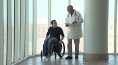 Man in wheelchair walking with doctor Stock Footage