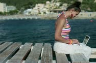 Happy woman sitting on pier with laptop computer, dolly shot Stock Footage