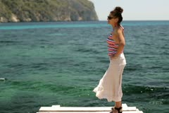 Young woman standing on pier by the sea Stock Footage