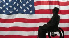 Silhouette of a soldier in a wheelchair in front of US flag Stock Footage