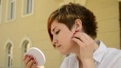 Young woman wears earrings and looks in the mirror Stock Footage