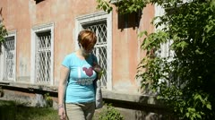 Young woman walks past an old brick house Stock Footage