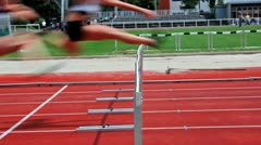 Loop and slow motion of female sprinter jumping over the hurdle Stock Footage