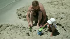 Father with son playing in sand on the beach Stock Footage