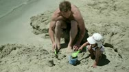 Stock Video Footage of Father with son playing in sand on the beach