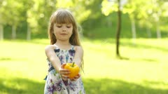 Child touts healthy eating. In the hands of the girl's a vegetable. Thumbs up Stock Footage
