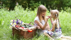 Mother and daughter with vegetables in nature. They eating cucumbers - stock footage