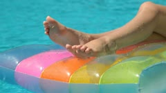 Female Legs on Pool Raft In Swimming Pool Stock Footage