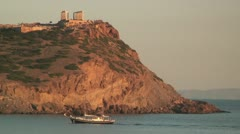 Yacht rounds Cape Sounion, Greece and the ancient Temple of Poseidon (Neptune) Stock Footage