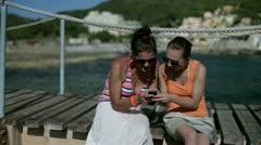 Happy female friends enjoying smartphone on pier, dolly shot Stock Footage