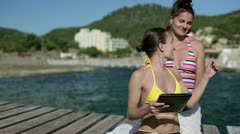Happy female friends sitting on pier with tablet computer, dolly shot Stock Footage