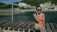 Happy woman sitting on pier and talking on cellphone, dolly shot Stock Footage