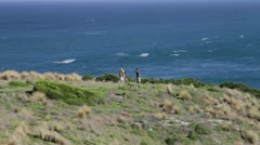 Pan left of 2 males walking with ocean in background Green Cape NSW Australia - stock footage