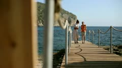 Happy female walking along the pier, dolly shot Stock Footage