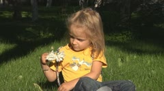 Child Smelling and Playing with Flowers in Park Stock Footage