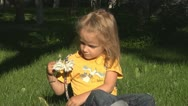 Stock Video Footage of Child Smelling and Playing with Flowers in Park