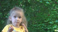 Little Blonde Girl Eating Cherries directly from the Cherry Tree in Orchard Stock Footage