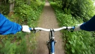 Pov riding mountain bike on trail in green forest Stock Footage