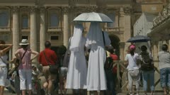 Two Nuns watch Pope's mass (2 clips) - stock footage