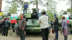 Civilian people look at military vehicles and panzers - stock footage