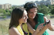 Stock Video Footage of Two smiling female friends with smartphone on terrace NTSC