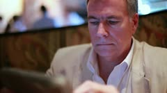 Businessman working with a tablet PC in a restaurant Stock Footage