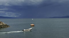 Man in Open Skiff Heading Out on Bay Storm Brewing Stock Footage