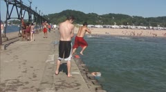 Teenage Boy Jumps Feet First off Pier in Lake Michigan, Part #3 Stock Footage