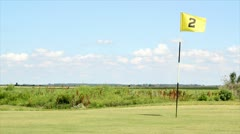 Golf field with yellow flag number two Stock Footage