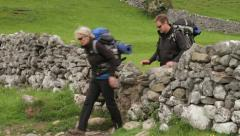 Hikers crossing dry stone wall, yorkshire dales Stock Footage