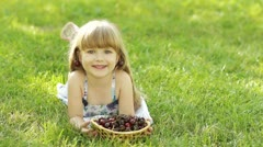 Child lying on the grass with a sweet cherry fruit Stock Footage