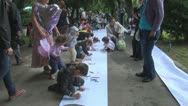 Stock Video Footage of Children Drawing in a Competition assisted by Their Parents in Park