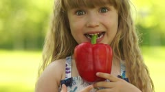Close-up portrait of a happy girl holding a vegetable in the teeth Stock Footage