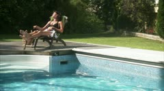 WS Woman on sunlounger relaxing on poolside Stock Footage