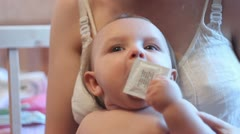 Baby plays with a condom Stock Footage