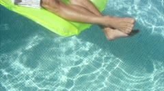 MS HA Man on air mattress floating on water in swimming pool Stock Footage