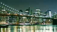 Stock Video Footage of Manhattan skyline and Brooklyn bridge at night. Time lapse and loopable
