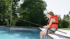 MS Girl wearing life jacket fishing on poolside Stock Footage