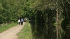 Elderly couple walking along canal tow path Stock Footage