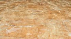Two people walking barefoot in water on marble floor Stock Footage