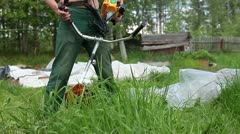 Man mowing green grass by weed trimmer Stock Footage