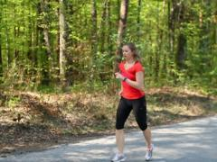 Young woman jogging with stopwatch in the forest, stedycam, slow motion Stock Footage
