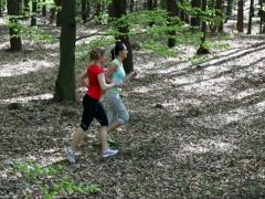 Two young women jogging in the forest, stedycam Stock Footage