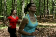 Two happy woman jogging in the forest, steadycam, slow motion Stock Footage